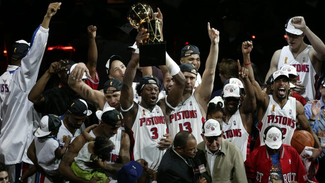 The Pistons celebrate with the Larry O'Brien trophy after knocking off the Lakers in Game 5 to win the 2004 title for the franchise's third NBA championship.