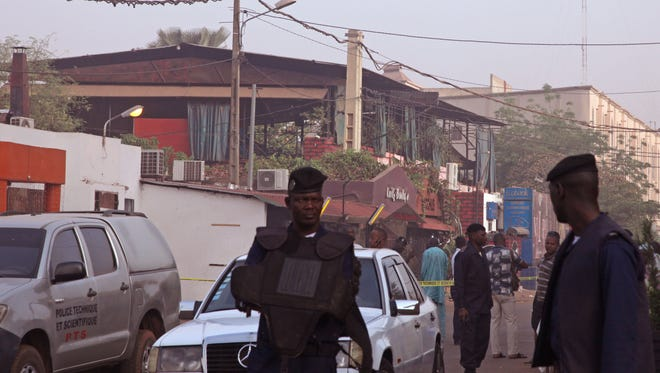 The nightclub, rear, that was attacked by gunmen as Mali police, center, provide security in Bamako, Mali on March 7, 2015.