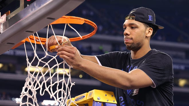 Duke's Jahlil Okafor cuts down the nets following the Blue Devils' 68-63 win over Wisconsin in the national championship game, April 6, 2015 at Lucas Oil Stadium.