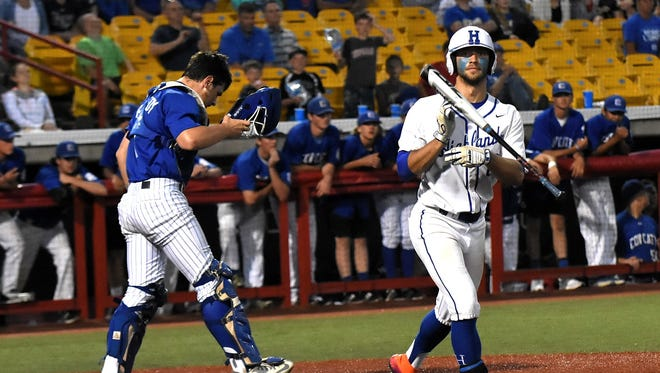 """As Covington Catholic's catcher Alex Kennedy walks off in disbelief, Drew Rom of Highlands flips the bat and heads to first base after the walk-off """"hit by pitch"""" that sealed the win for the Bluebirds at the KHSAA 9th Region Championship, May 31, 2018."""