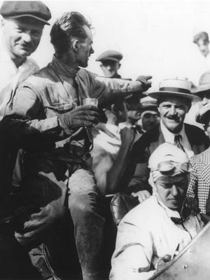 Tommy Milton (seated in car with goggles) won the 1921 Indianapolis 500.  Riding mechanic Harry Franck waves to the crowd. Louis Chevrolet (in straw hat) looks on.