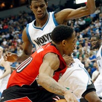 The Toronto Raptors' DeMar DeRozan, front, drives around the Minnesota Timberwolves' Andrew Wiggins in the second half Wednesday in Minneapolis. The Raptors won 113-99.
