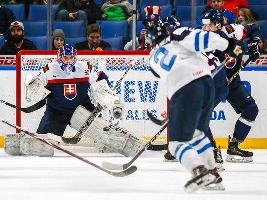 FILE - In this Dec. 30, 2017, file photo, Slovakia goalie Roman Durny, left, takes a shot from Finland's Miro Heiskanen, right, during the second period of IIHF World Junior Championship preliminary hockey action in Buffalo, N.Y. First-round draft picks Heiskanen and Eeli Tolvanen are ready to show what they've got for Finland at the Olympics and are expected to play in the NHL sooner rather than later. (Mark Blinch/The Canadian Press via AP, File)