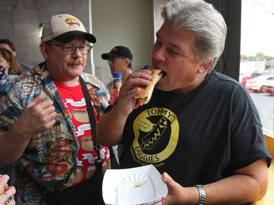 One of the organizers, John Fox, bites into a dog at Cioffi's Boardwalk in Union during the the 12th Annual Hot Dog Tour. At left is Mo Cooper of San Francisco.