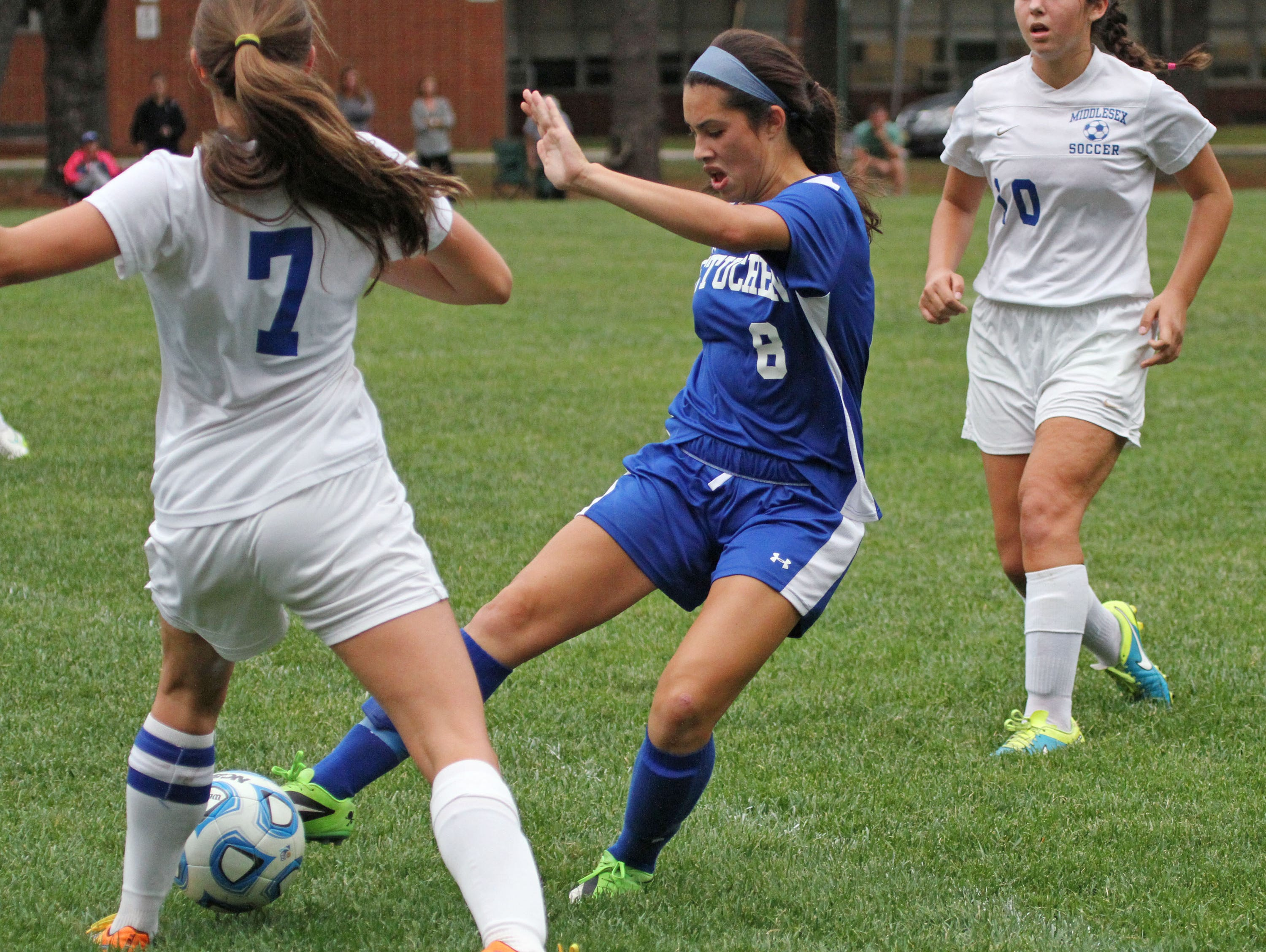 Metuchen's Taylor Hueston, center, controls the ball as Katie LaCapria, left, challenges in girls soccer game at Middlesex. Hueston scored for her team.