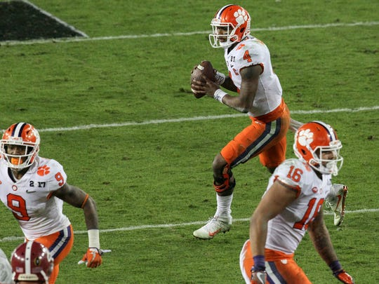 Clemson quarterback Deshaun Watson (4) rolls right to throw to receiver Hunter Renfrow (13) for the winning touchdown during the fourth quarter of the National Championship game on Monday at Raymond James Stadium in Tampa, Florida.