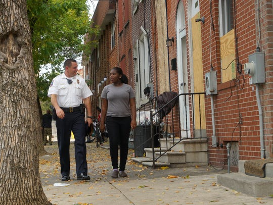 Wilmington police officer Lt. Dan Selekman walks down N. Monroe Street with 16-year-old Dashnany Howell, who he was able to get a job at McDonald's.