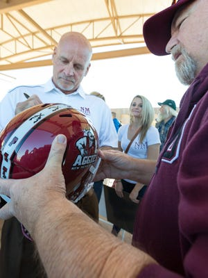 Steve Dail, of Las Cruces, has his helmet signed by NMSU head football coach Doug Martin on Saturday, January 20, 2018, during an Aggies celebration at Plaza de Las Cruces.