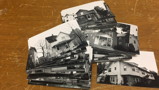 Old photos of Post Addition homes lay scattered in the Historical Society of Battle Creek's offices.