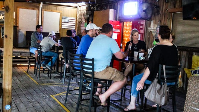 Patrons sip on drinks on the outdoor patio at Hanovers Draught Haus in downtown Pflugerville Thursday evening.