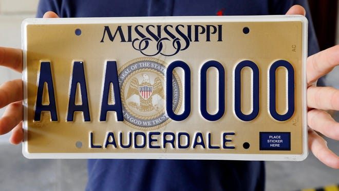 """Clay Chandler, director of communications for Gov. Phil Bryant, holds Mississippi's new standard license plate Thursday, May 10, 2018, at the Capitol in Jackson, Miss. It will display the state seal that includes the phrase, """"In God We Trust."""""""