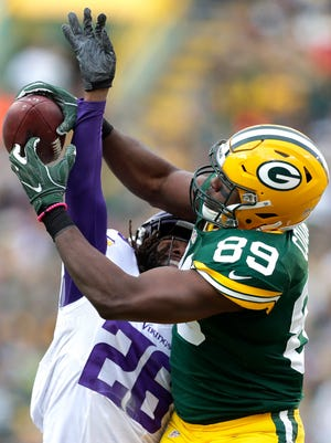 Jared Cook catches a pass for a first down in front of Trae Waynes.
