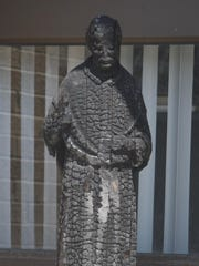 The burned statue of St. Pius X was found after the fire and now sits outside the parish office.