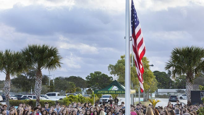 Students at Jupiter High School gather around a flag at half mast during a ceremony to remember the victims of the Parkland shooting in 2018.