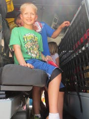 Seth Boegel enjoyed sitting in a Campbellsport Fire Department truck during a Campbellsport Public Library summer reading program. More than 100 kids had a great time visiting the fire station.
