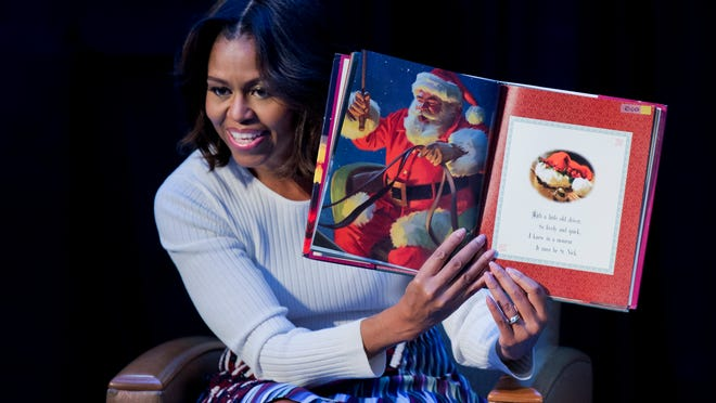 "In this Dec. 15, 2014, photo, first lady Michelle Obama, reads ""Twas the night before Christmas"" to patients, families, and staff at Children's National Health System in Washington."