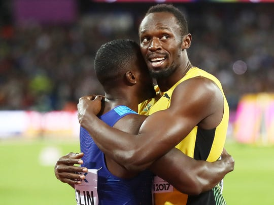 Usain Bolt, of Jamaica, hugs Justin Gatlin after Gatlin's