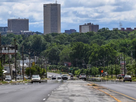 Heat rises off the asphalt near downtown Greenville, where one lane has new asphalt and another not yet. Cars drive on Wade Hampton Boulevard during the day, before evening road work to put down new asphalt.