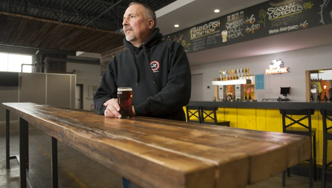 Gene Muller, founder and general manager of Flying Fish Brewing Company, enjoys a beer in his Somerdale brewery. Flying Fish will partner with a Philadelphia developer and chef to create a pub in Brewerytown.