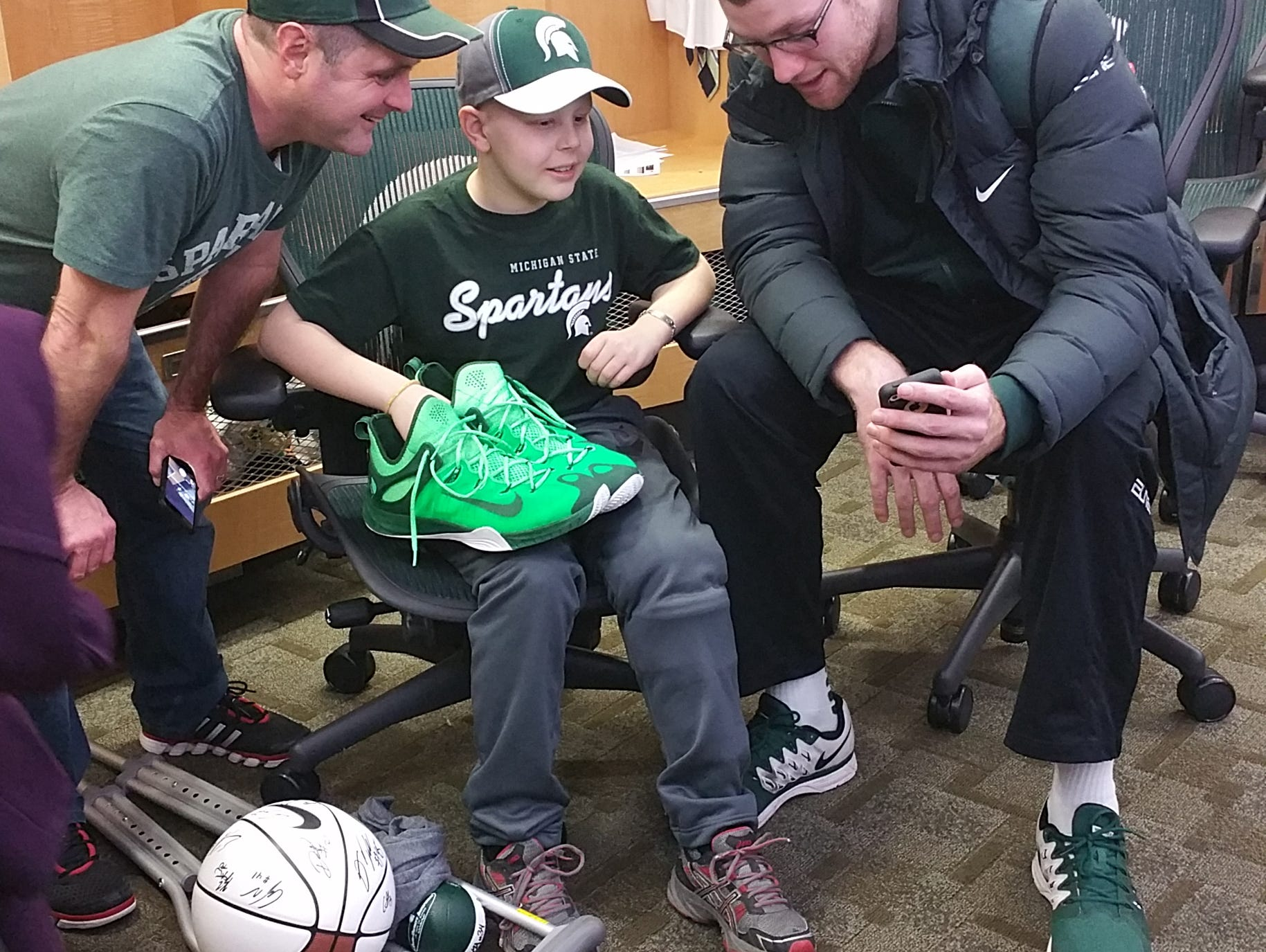 Mike McGuire, MacKale McGuire and MSU basketball player Matt Costello share a locker-room moment after Thursday's game against Illinois.