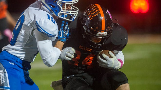Brighton's Joe Salvato (34)  is pushed out of bounds by Walled Lake Western's Matt Alati (19) during Walled Lake Western's 37-7 win in Brighton for the Kensington Lakes title Friday.
