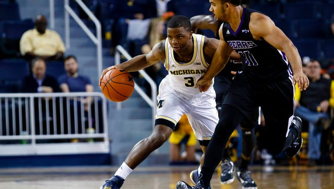 Michigan guard Xavier Simpson (3) dribbles defended by Central Arkansas guard Jeff Lowery (11) in the first half Tuesday at Crisler Center.