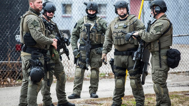 SWAT team members stand outside of a residence after a drug raid Thursday afternoon.