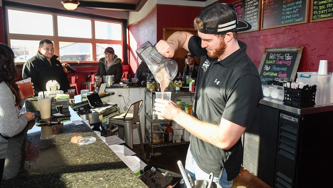 Travis Stoerzinger mixes an energy drink for a customer Wednesday, Jan. 31, at the new Flat Iron Nutrition.