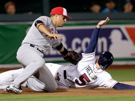 Miami Marlins third baseman Martin Prado misses the tag as Atlanta Braves' Freddie Freeman (5) slides safely into third base during the fourth inning of a baseball game in Fort Bragg, N.C., Sunday, July 3, 2016. (AP Photo/Gerry Broome)