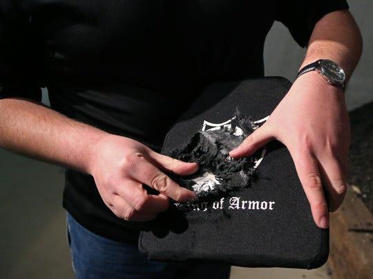 Blake Waldrop, CEO of RMA Armament, holds a body armor