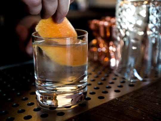 Mike McDonald places an orange peel in a cocktail at
