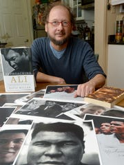 """Author Davis Miller poses with a collection of photos of boxer Muhammad Ali and his newest book about the man, titled """"Approaching Ali,"""" at his home in Asheville. Miller has a unique relationship and some of the print outs include screen grabs from a video of Ali playing with Miller's son."""