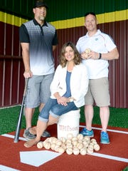 Part of the D-BAT Asheville team, James Thomas, baseball coach, left, Erin Secretarski, co-owner, center, and Rusty Bell, manager, right, stand at what will be a batting lane at the new baseball and softball training facility on Hendersonville Road. D-BAT stands for developing beliefs, attitudes and traditions and owners hope to not only build skills but character in their young clients.
