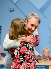 Donna Pate hugs her niece, Marcella Montgomery, 10, after being sworn in to the Buncombe County School Board at the Buncombe County Schools central office on Thursday, Dec. 1, 2016.