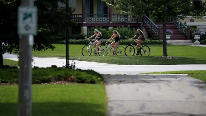 Kim Remington of Cedarburg, left, rides her bike with her friend Lindsey Coons of Neenah and sister Erika Remington of Cedarburg on Wisconsin Avenue in Neenah. The route is part of the Fox Cities Paper Trail.