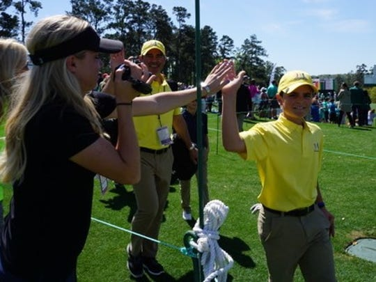 Logan Gonzalez gives a high-five to his mother, Tatiana, at the Drive, Chip and Putt finals at Augusta National.