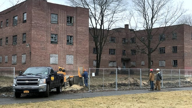 Crews remove tree stumps as part of the rehabilitation project at the former Jones Court apartment complex in Elmira.