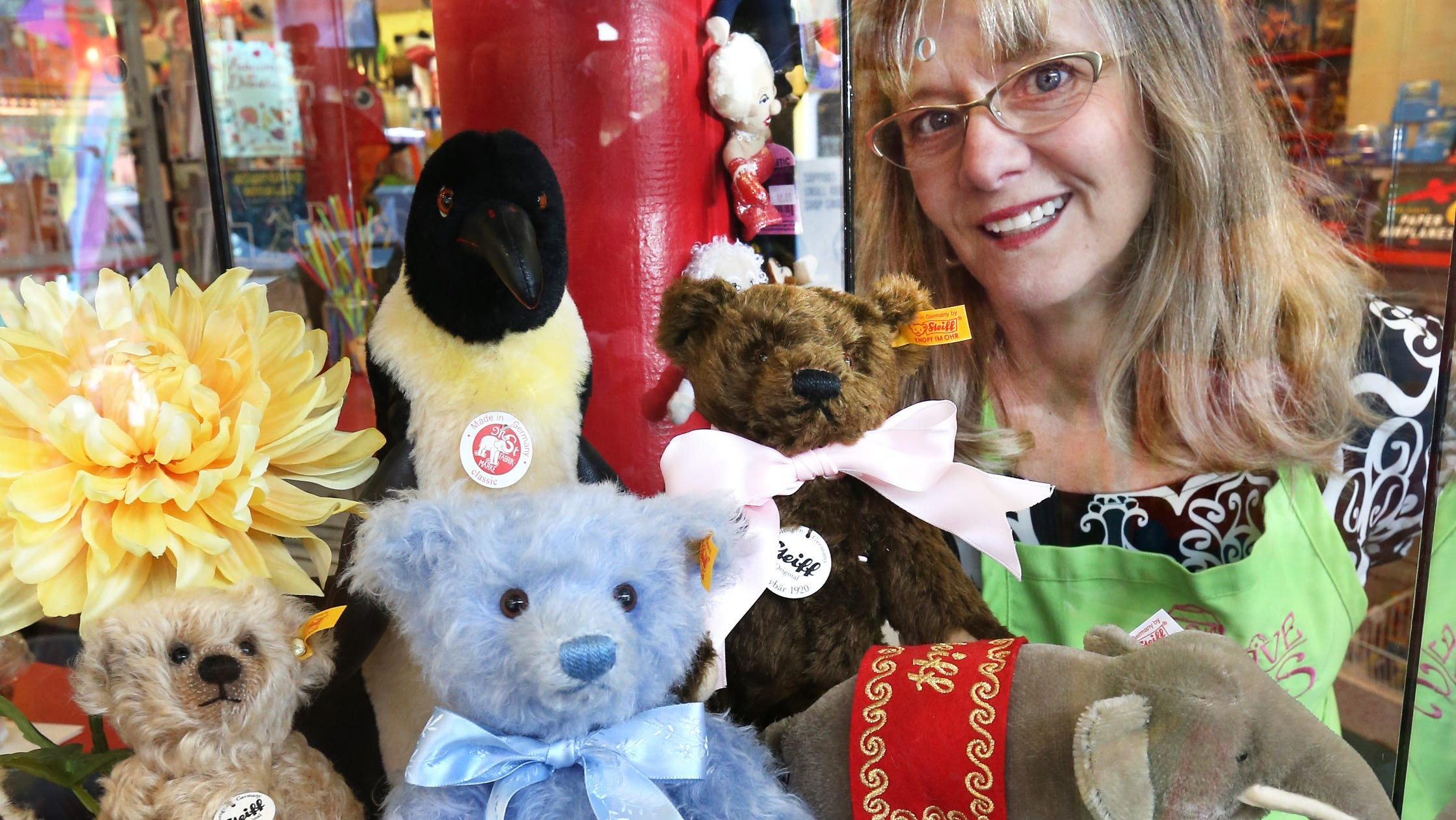Mass Ave Toys owner Natalie Canull, who opened the independent business at 409 Mass Ave. is 2008, is shown with classic German-made Steiff teddy bears on Tuesday, July 1, 2014.