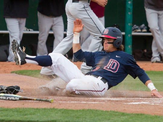 Dixie State second baseman Drew McLaughlin slides home