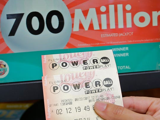 A customer shows her purchased Powerball tickets for