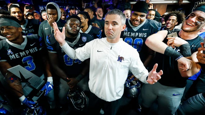 Memphis head coach Mike Norvell, middle, chats with his players in the locker room after defeating SMU 66-45 to win the American Athletic Conference West Division Championship in Memphis on Nov. 18, 2017.