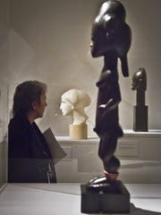 A visitor views African and European sculptures during a media preview at the Jewish Museum in New York.