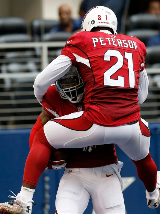 After interception the ball against the Dallas Cowboys, Arizona Cardinals cornerback Antonio Cromartie, left, celebrates with cornerback Patrick Peterson (21) during the second half of an NFL football game Sunday, Nov. 2, 2014, in Arlington, Texas. (AP Photo/Sue Ogrocki)