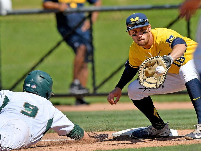 Michigan first baseman Jake Bevins gets the ball, but