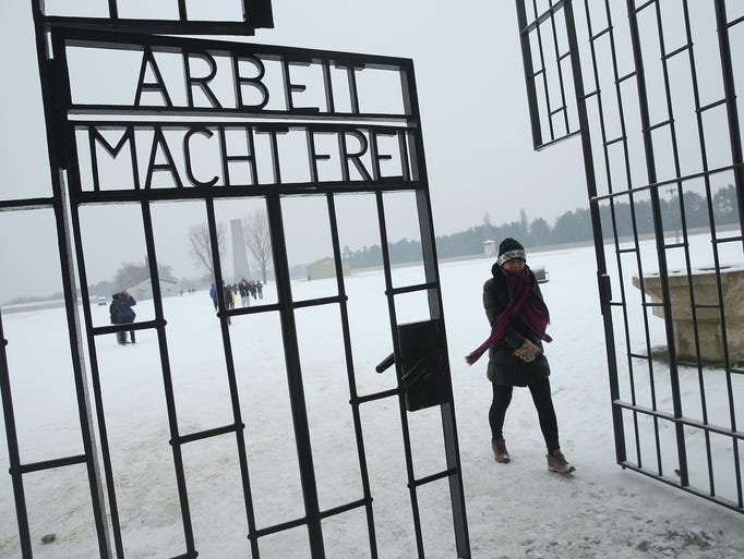 """A visitor walks past an inscription that reads, """"Arbeit Macht Frei,"""" which means """"Work Leads To Freedom,"""" at the gate of Sachsenhausen concentration camp, whose gate and remaining buildings stand as a memorial, on International Holocaust Remembrance Day on Jan. 27 in Oranienburg, Germany. Sachsenhausen operated from 1933 until 1945."""