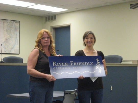 Jenelle Ditzel receives a sign announcing the certification of her farm from Kara Hosko of North Jersey Resource Conservation and Development.