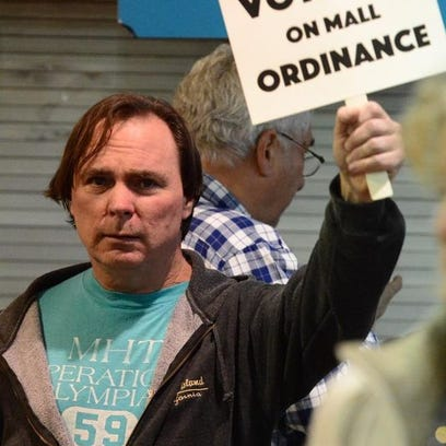 A member of the public holds a sign against an ordinance