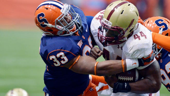 Syracuse Orange linebacker Marqez Hodge (33) makes a tackle on Boston College Eagles running back Andre Williams (44) during the first quarter of a game at the Carrier Dome.