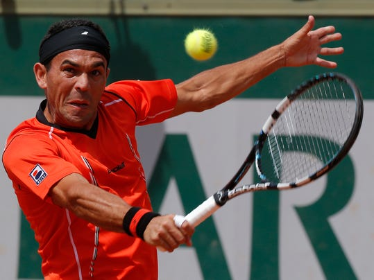 Dominican Republic's Victor Estrella Burgos backhands to Poland's Jerzy Janowicz during their first round match of  the French Open tennis tournament at the Roland Garros stadium, in Paris, France, Sunday, May 25, 2014. (AP Photo/Michel Euler)
