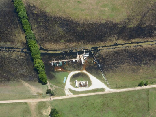 As floodwaters recede on the Lower Trinity River last year, what appears to be oil remains around a production site. The Texas Department of Public Safety earlier this month removed such photos from a public website, citing privacy concerns.